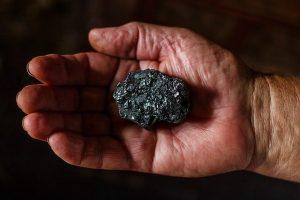bryłka węgla na dłoni