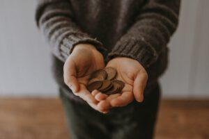 Człowiek trzymający w dłoni monety