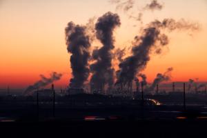 dym z kominów fabryki na tle zachodzącego słońca