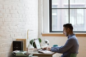 mężczyzna pracujący przy laptopie